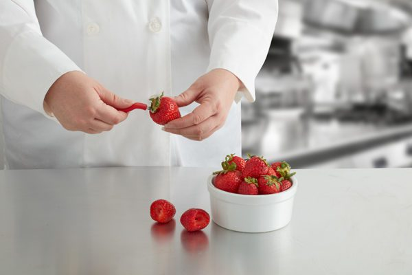 coring a strawberry in a chef's kitchen