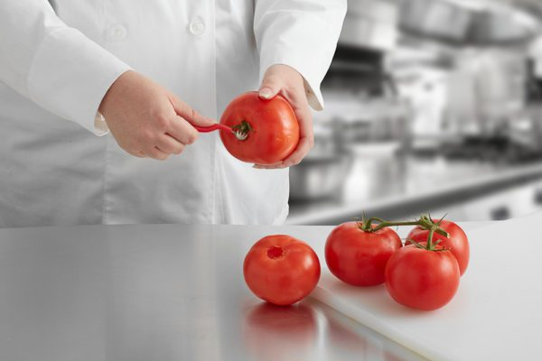 coring a tomato in a chef's kitchen